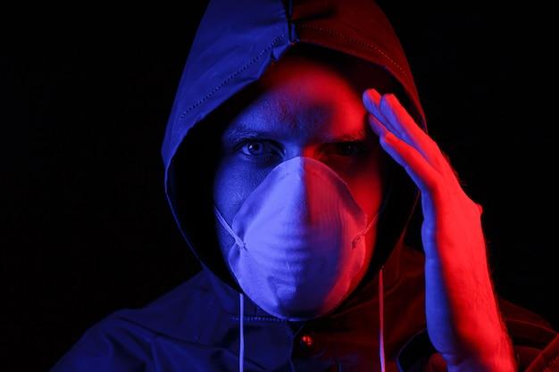 Um homem com uma roupa protetora de borracha e uma máscara médica branca. proteção contra vírus. iluminado em vermelho e azul.