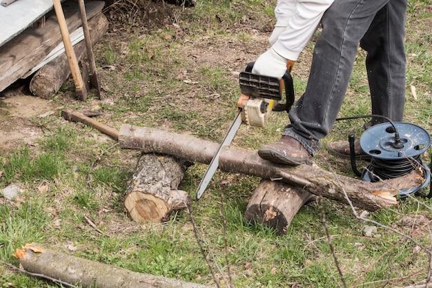 Um homem com uma serra elétrica corta uma árvore para tirar lenha no jardim.