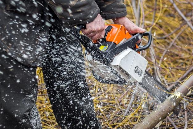 Um homem com uma serra elétrica cortando um tronco, derrubando uma floresta, colhendo lenha