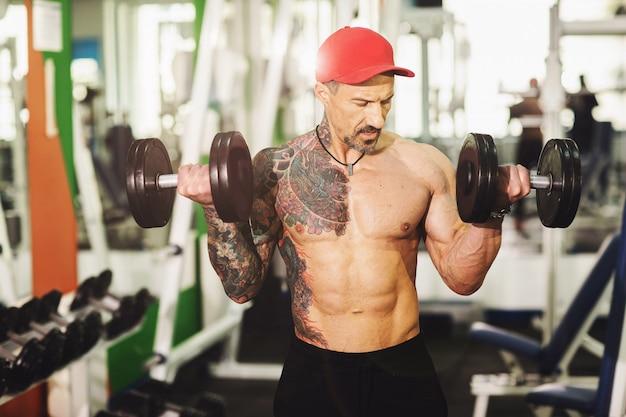 Um homem com uma tatuagem em um ginásio. execute o exercício com halteres no ginásio colorido