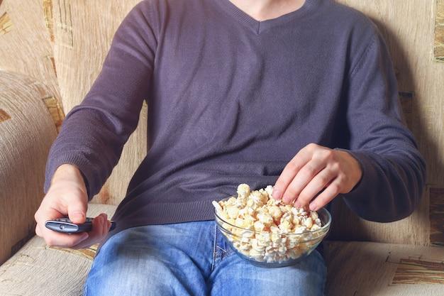 Um homem com uma tigela de pipoca e um controle remoto na mão olha para a tv no sofá.