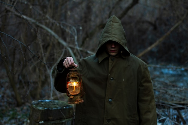 Um homem com uma velha lanterna brilhante em uma capa de chuva em uma floresta escura. silhueta de um culto, uma pessoa realiza um ritual em uma floresta mágica. o conceito de ocultismo. foco suave