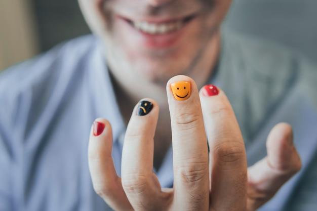 Um homem com unhas pintadas. desenho de unhas masculinas. manicure dos homens. foco na unha
