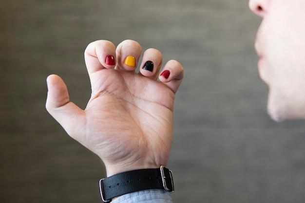 Um homem com unhas pintadas. desenho de unhas masculinas. manicure dos homens.