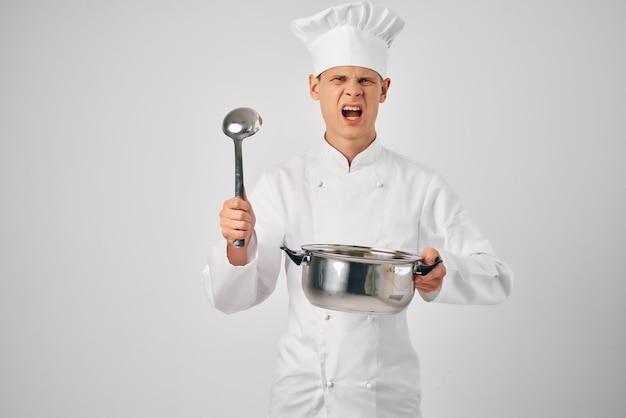 Um homem com uniforme de chef com uma panela e uma concha nas mãos preparando comida