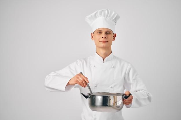 Um homem com uniforme de chef com uma panela nas mãos preparando comida em restaurante