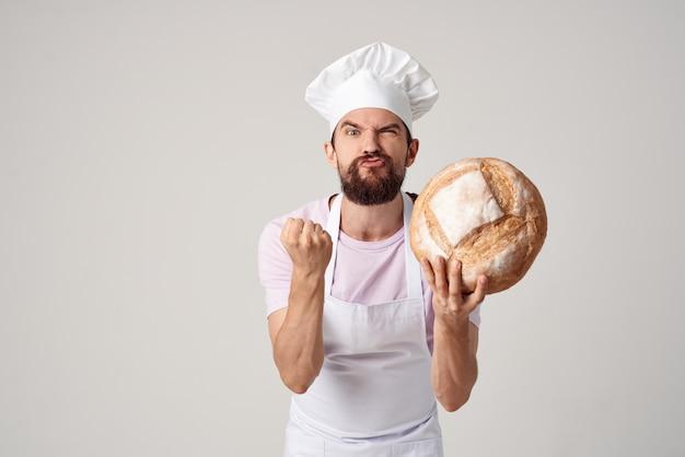 Um homem com uniforme de padeiro cozinhando pão