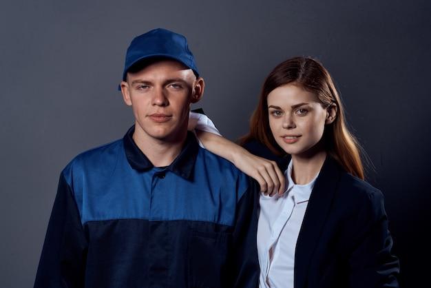 Um homem com uniforme de trabalho ao lado de uma mulher em uma equipe de trabalho de escritório de terno