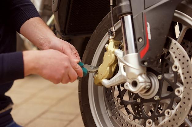 Um homem conserta motocicleta no serviço