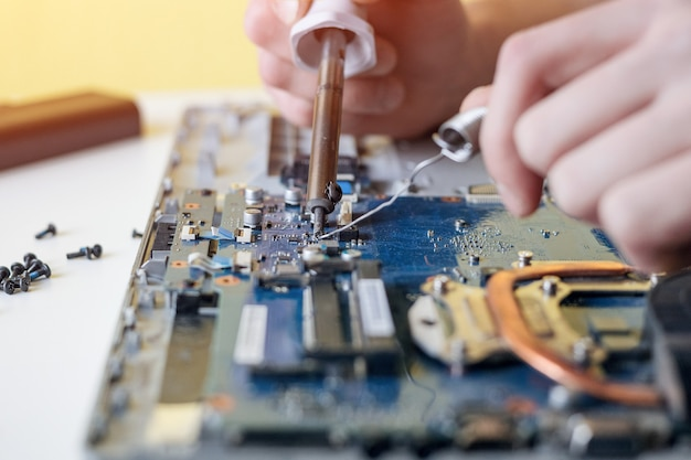 Um homem conserta um laptop, desmonta um laptop em uma parede branca e solda a placa-mãe do laptop