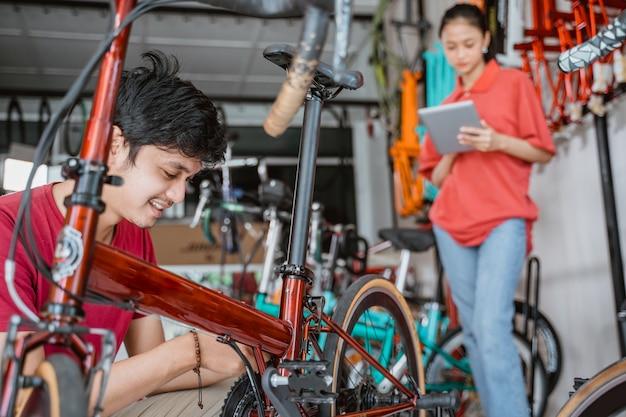 Um homem conserta uma bicicleta com uma mulher ao fundo usando um teclado digital