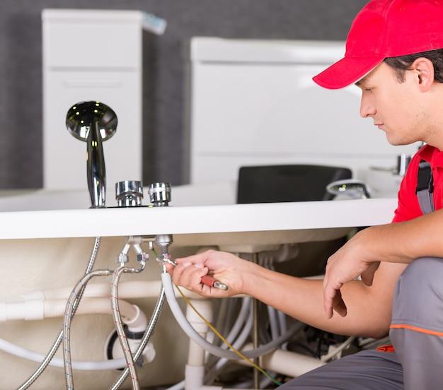 Um homem conserta uma pia quebrada em casa.
