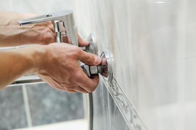 Um homem conserta uma torneira no banheiro