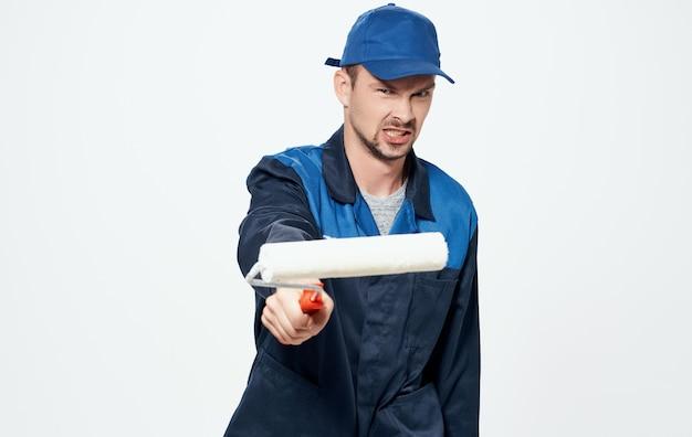 Um homem conserta vidros amarelos e um rolo para pintar as paredes.