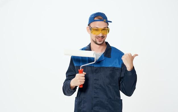 Um homem conserta vidros amarelos e um rolo para pintar as paredes