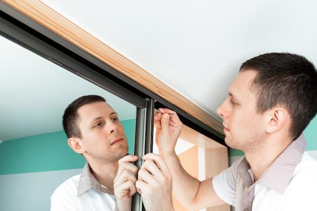 Um homem consertando uma maçaneta