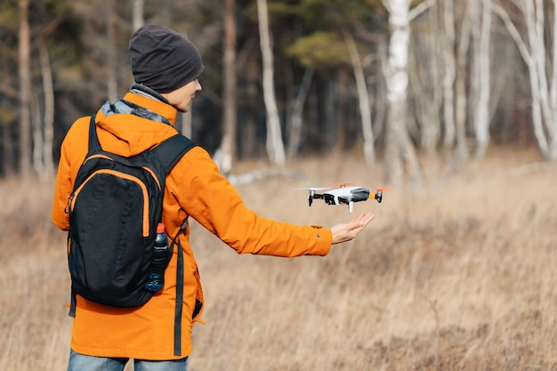 Um homem controla um zangão quadcopter ao ar livre no outono. o cara estende a mão para o drone.