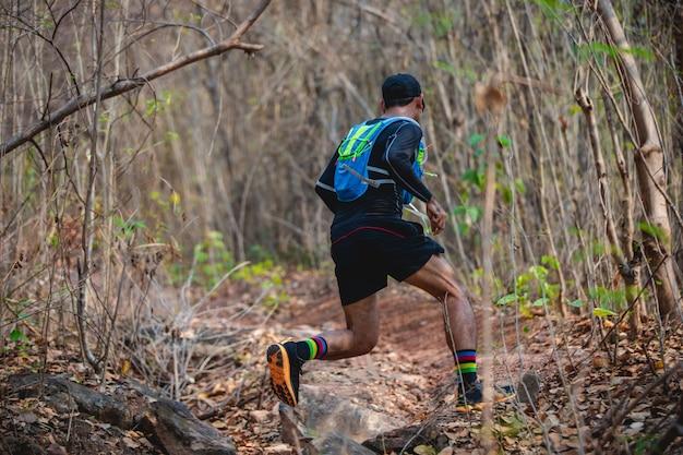 Um homem corredor de trilha. e pés de atleta usando sapatos esportivos para trilha correndo na floresta