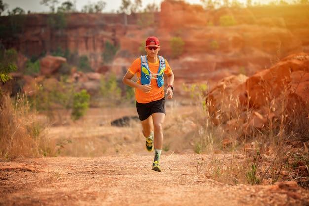 Um homem corredor de trilha e pés de atleta usando sapatos esportivos para trilha correndo na floresta