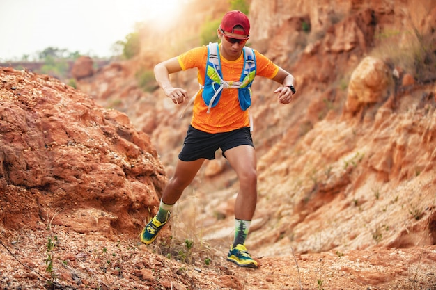 Um homem corredor de trilha. e pés de atleta usando sapatos esportivos para trilha correndo nas montanhas