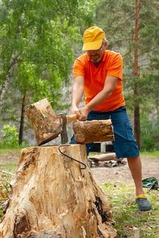 Um homem corta lenha com um machado para fazer uma fogueira durante uma caminhada.