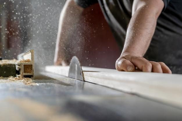 Um homem corta madeira em uma serra circular em uma marcenaria