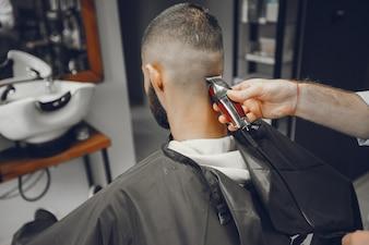 Um homem corta o cabelo em uma barbearia.
