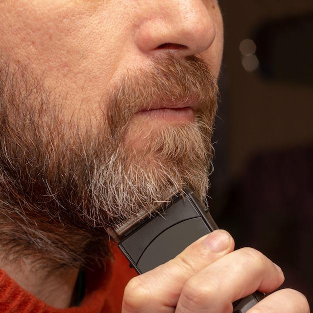 Um homem corta seu aparador de barba cinza close-up