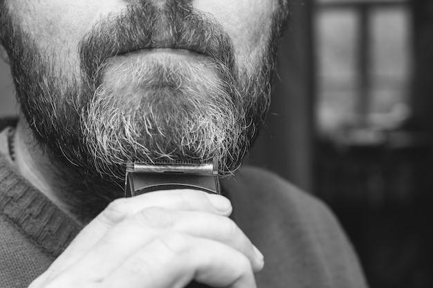 Um homem corta seu cinza barba aparador closeup, foto preto e branco