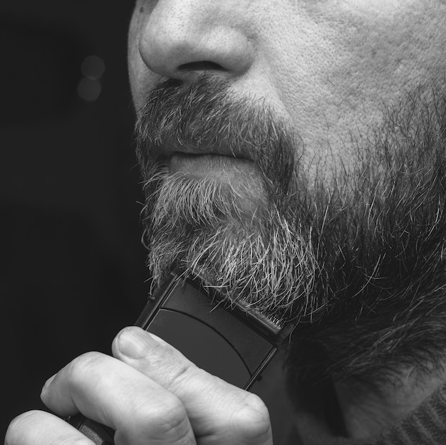 Um homem corta sua foto de close-up, preto e branco de aparador de barba grisalha