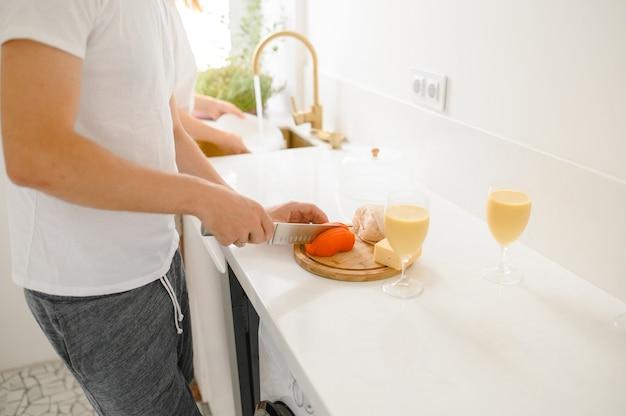 Um homem corta tomates em uma tábua em uma cozinha bem iluminada.
