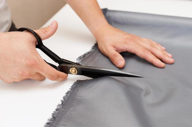 Um homem corta um tecido com uma tesoura em um close-up da mesa