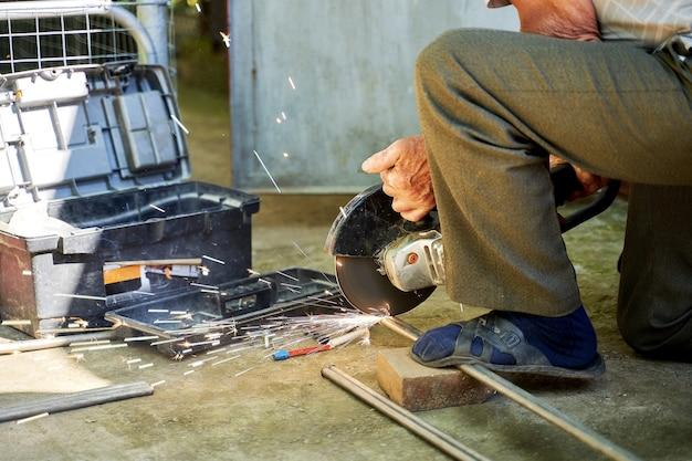 Um homem corta um tubo de titânio com um moedor.