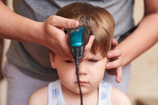 Um homem corta uma máquina de criança em casa