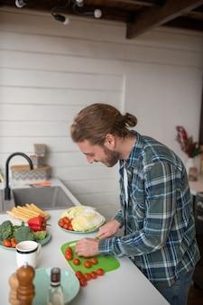 Um homem cortando tomates cereja para uma salada fresca