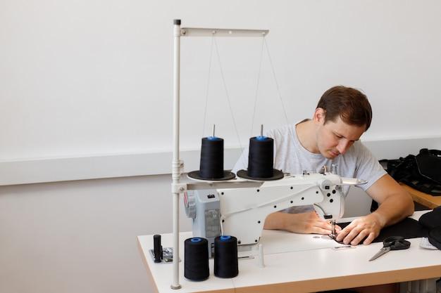 Um homem costura atrás de uma máquina de costura na produção