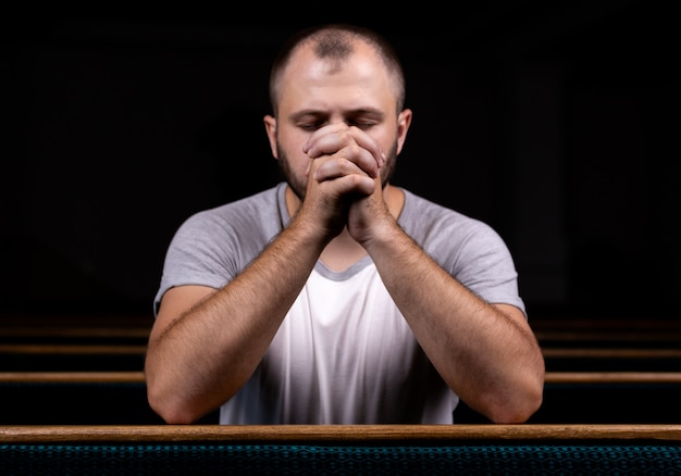 Um homem cristão de camisa branca está sentado e orando com coração humilde na igreja