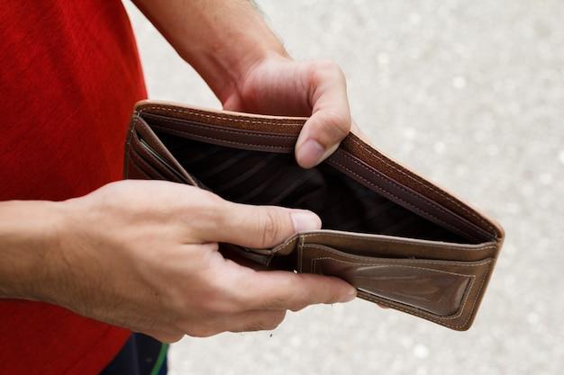 Um homem da mão do close up abre uma carteira vazia.