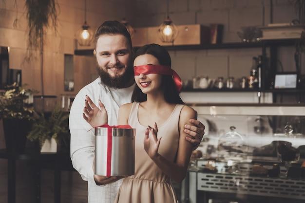 Um homem dá um presente para uma menina com os olhos fechados