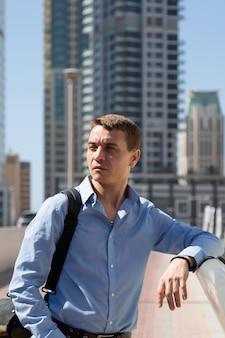Um homem de 35 a 40 anos está parado no centro de uma cidade grande e olha ao redor com interesse.