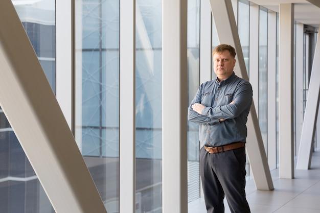 Um homem de 40-45 anos com uma camisa xadrez azul posa no corredor dos fundos do escritório em meio a uma grande janela