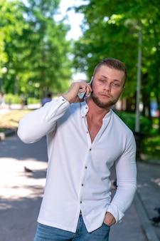 Um homem de aparência europeia caminha no parque e fala ao celular