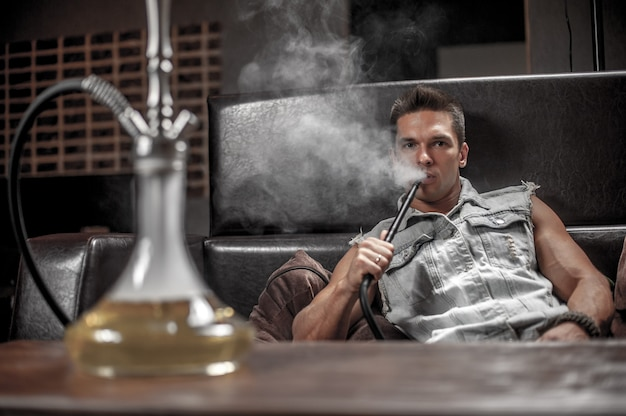 Um homem de aparência europeia soprando nuvens de fumaça no restaurante árabe.