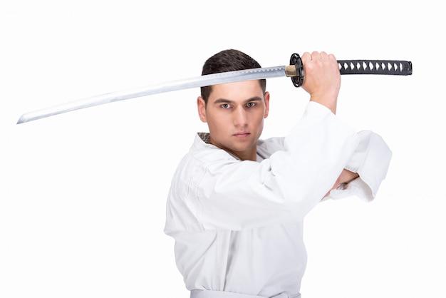 Um homem de artes marciais está de pé com uma espada.