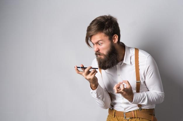 Um homem de barba de camisa branca e suspensórios amarelos grita ao telefone, indignado, tentando explicar sua ideia sobre um fundo cinza