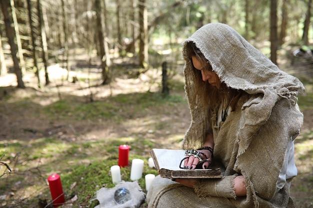 Um homem de batina passa um ritual em uma floresta escura com uma bola de cristal e um livro