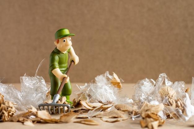 Um homem de brinquedo em um terno de trabalhador varre uma grande quantidade de lixo. conceito de proteção e ecologia ambiental.
