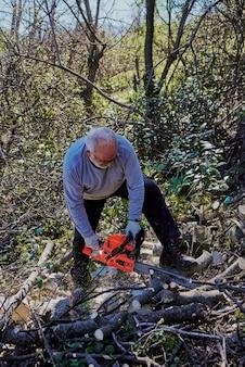 Um homem de cabelo branco está cortando lenha na floresta