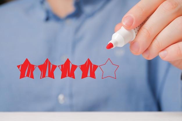 Um homem de camisa abstrai uma classificação de quatro estrelas em cinco com um marcador. boa marca