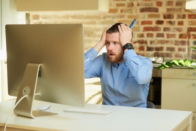 Um homem de camisa azul chocado com os preços de uma loja on-line e colocando as mãos com um cartão de crédito na cabeça